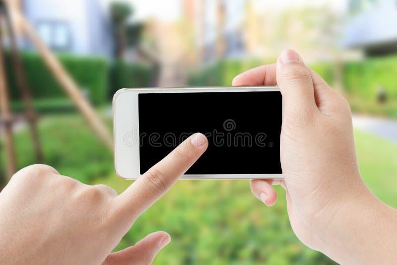 Conceito de smartphone tocante da mão da mulher no jardim fotografia de stock royalty free