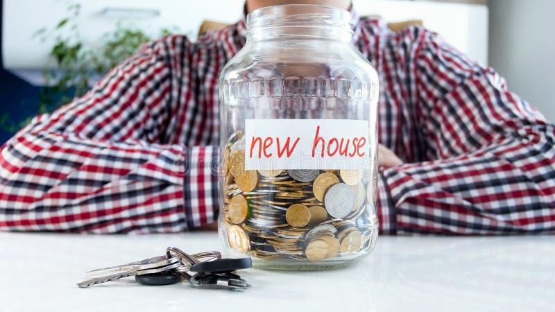 Conceito de tomar o crédito bancário para comprar a casa nova Homem com o frasco de vidro completo do dinheiro e dos keas do apar fotografia de stock