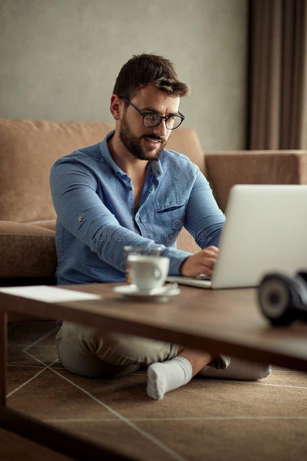 Conceito de trabalho da casa - homem que usa um laptop para o trabalho em ho fotos de stock royalty free