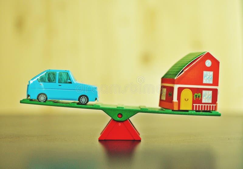 Conceito de um equilíbrio entre um carro e uma casa no fundo verde imagens de stock royalty free