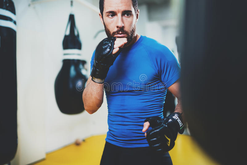 conceito de um estilo de vida saudável Pontapés praticando do lutador muscular novo do homem com perfuração do saco preto Encaixo fotos de stock