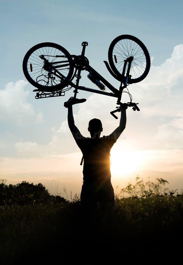 Conceito de um estilo de vida ativo cycling Silhueta do ciclista com os braços aumentados até o céu foto de stock