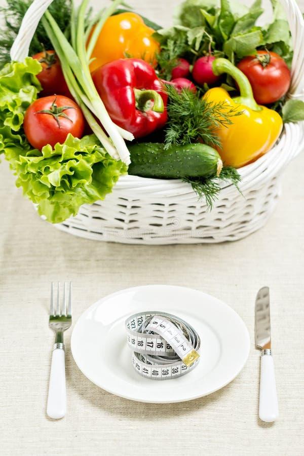 Conceito de uma dieta saudável A cesta dos vegetais e de uma placa imagens de stock