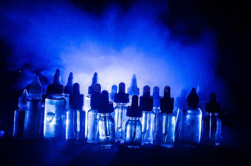 Conceito de Vape Nuvens de fumo e garrafas líquidas do vape no fundo escuro Efeitos da luz fotografia de stock