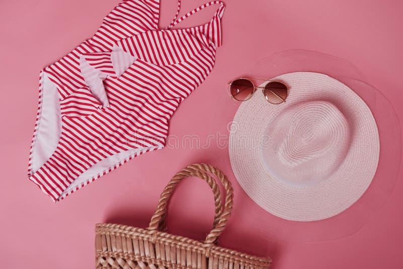 Conceito de viagem e férias Bikini na mesa cor-de-rosa Grupo de objetos para viagens e foto de stock royalty free