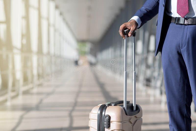 Conceito de viagem Homem africano que mantém sua mala de viagem no aeroporto, fim fotografia de stock royalty free