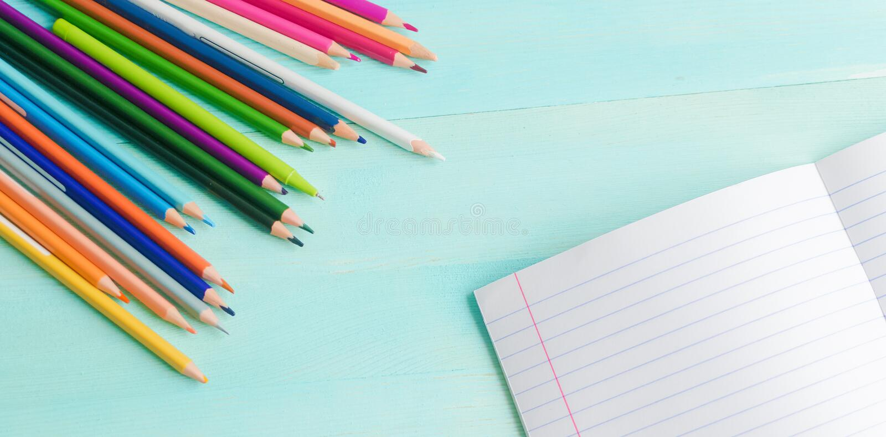 Conceito de volta ? escola Acessórios da escola, lápis coloridos, pena com o caderno vazio no fundo de madeira azul foto de stock