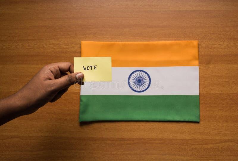 Conceito de votação - etiqueta de votação escrita mão da terra arrendada da pessoa na bandeira da Índia imagens de stock royalty free