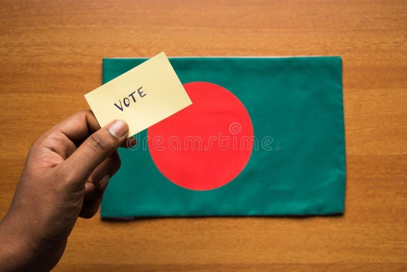 Conceito de votação - etiqueta de votação escrita mão da terra arrendada da pessoa na bandeira de Bangladesh fotos de stock royalty free