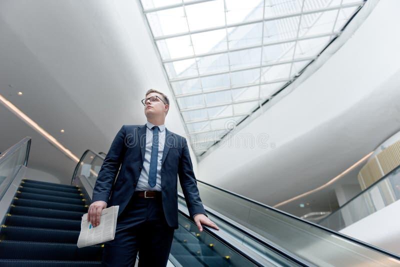 Conceito de Walking Down Escalator do homem de negócios imagem de stock