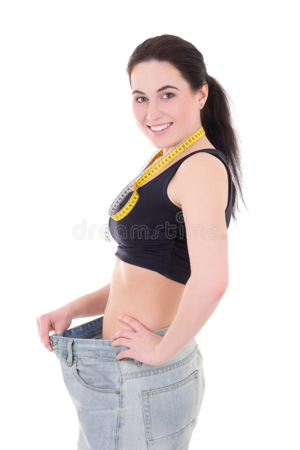 Conceito de Weightloss - mulher magro bonita feliz no iso grande das calças de brim fotos de stock royalty free