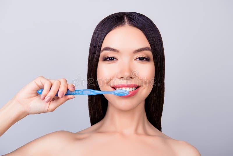 Conceito dental da saúde A menina asiática lindo está limpando seus dentes fotos de stock royalty free