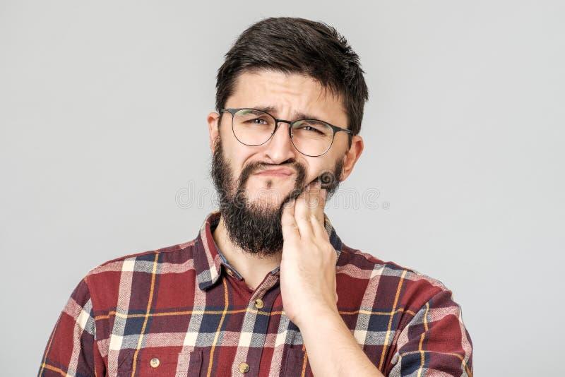 Conceito dental e da sa?de Retrato da mão atrativa incomodada da terra arrendada do homem no dente foto de stock