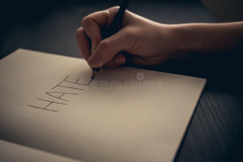 Conceito do ódio - entregue o ódio da escrita no livro imagem de stock royalty free