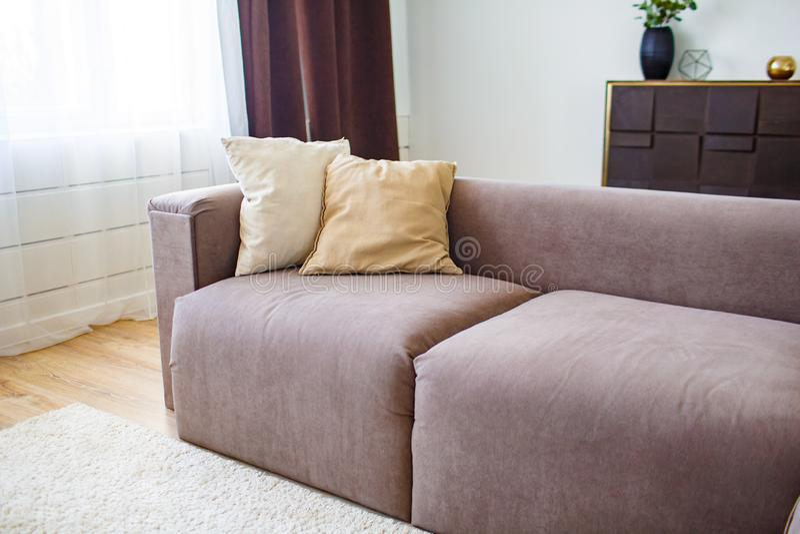 Conceito do abrandamento Cushiong dois que encontra-se no sofá marrom no interior moderno fotografia de stock