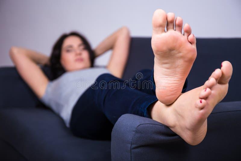 Conceito do abrandamento - jovem mulher que encontra-se no sofá em casa imagem de stock