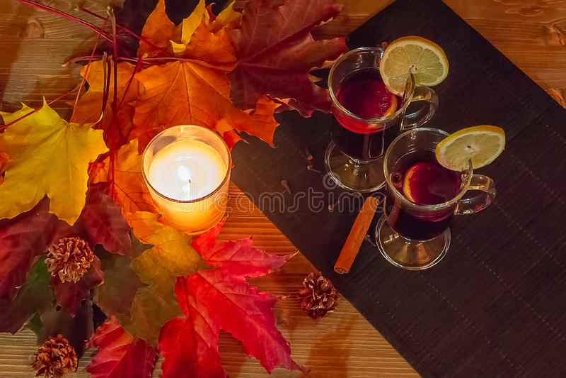 Conceito do abrandamento do outono Dois vidros do vinho ferventado com especiarias e de uma vela ardente cercada pelas folhas de  foto de stock royalty free