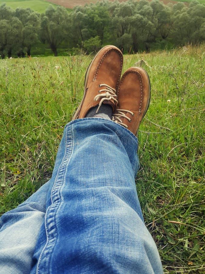 Conceito do abrandamento, pés do homem na grama durante sereno ensolarado fotografia de stock