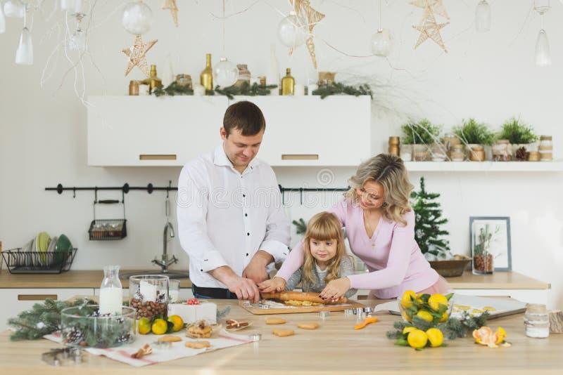 Conceito do alimento, da família, do Natal, do hapiness e dos povos - família de sorriso que faz uma cookie do pão-de-espécie no  imagens de stock