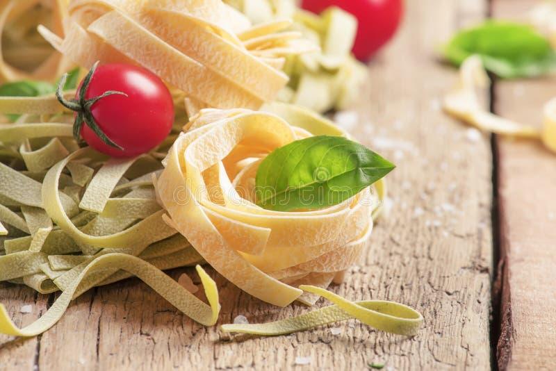 Conceito do alimento italiano que cozinha com massa verde e amarela dos tagliatelle, o tomate de cereja vermelho e manjericão ver fotografia de stock royalty free