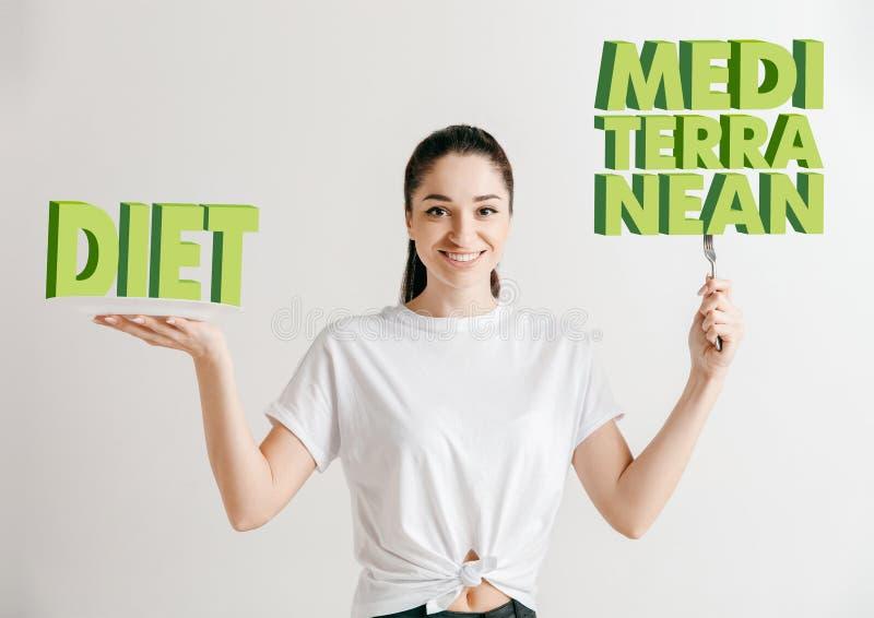 Conceito do alimento Modelo guardando uma placa com as letras da dieta, mediterrâneas foto de stock
