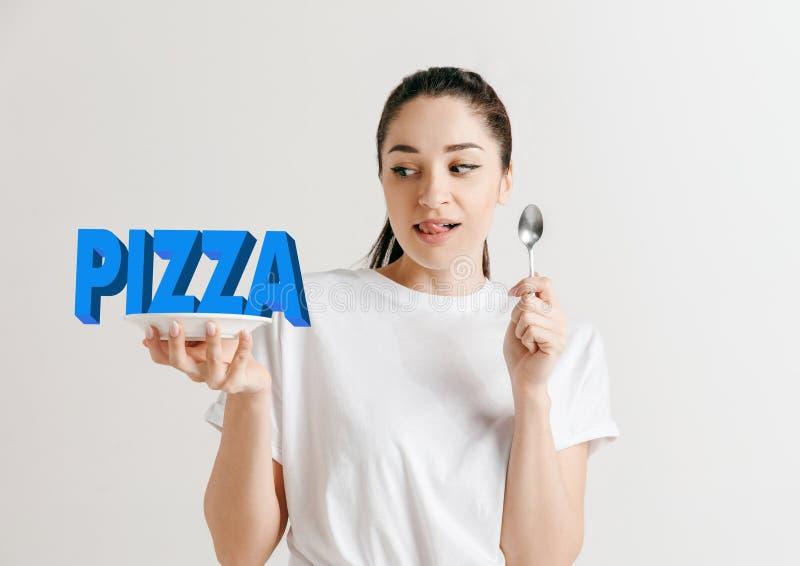 Conceito do alimento Modelo guardando uma placa com letras da pizza imagens de stock royalty free