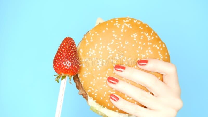 Conceito do alimento saud?vel e insalubre Morangos contra Hamburger em um fundo azul brilhante m?os f?meas com fotos de stock royalty free