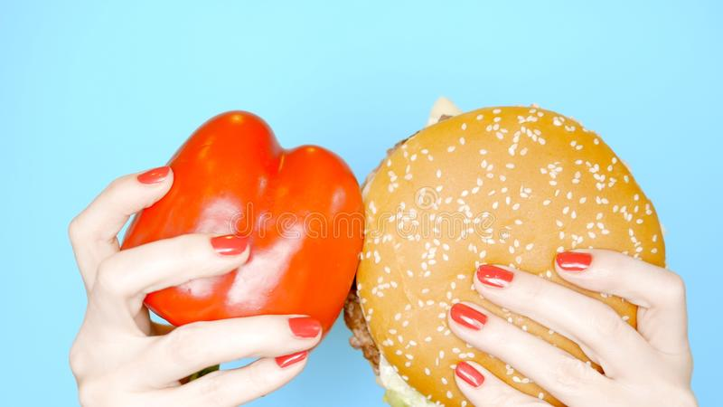 Conceito do alimento saud?vel e insalubre pimenta vermelha doce contra Hamburger em um fundo azul brilhante M?os f?meas imagem de stock