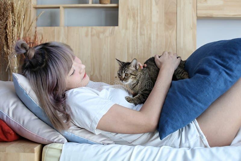 Conceito do amante do gato Mulher asiática bonita que senta-se no sofabed e que leva um gato em sua mão com amor Menina bonito e  foto de stock royalty free