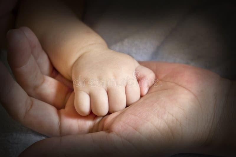 Conceito do amor e da família Mãos da matriz e do bebê foto de stock