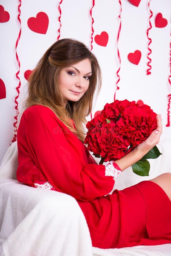 Conceito do amor - mulher lindo no vestido vermelho com flores foto de stock