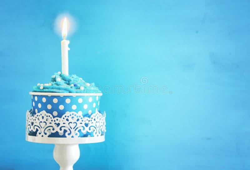 Conceito do aniversário com queque e uma vela na tabela de madeira imagens de stock royalty free