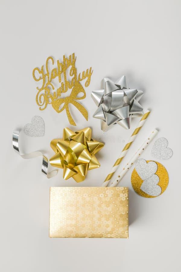 Conceito do aniversário - decorações douradas do abd da caixa no fundo branco fotografia de stock royalty free