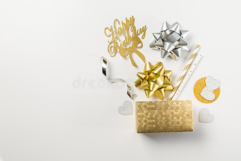 Conceito do aniversário - decorações douradas do abd da caixa no fundo branco imagem de stock