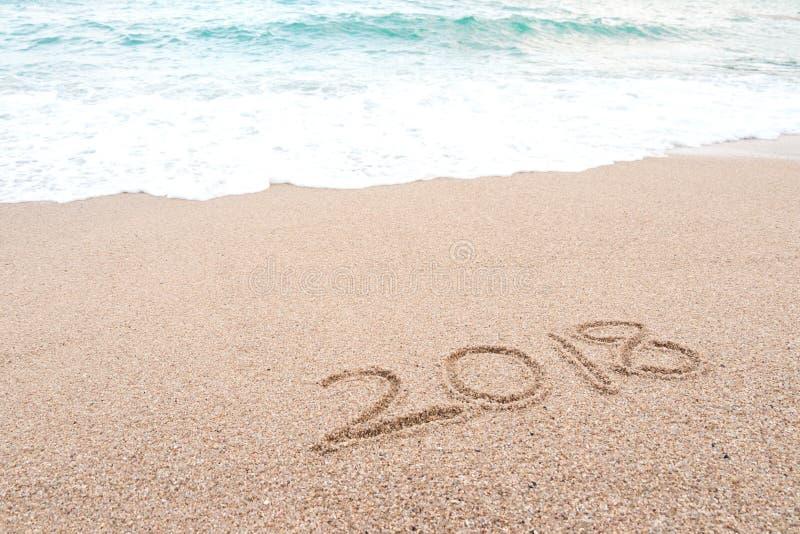 Conceito 2018 do ano novo feliz Número 2018 escrito no Sandy Beach imagem de stock