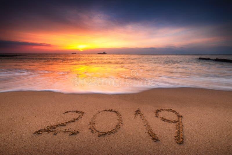 Conceito 2019 do ano novo feliz, rotulando na praia Nascer do sol do mar fotos de stock royalty free