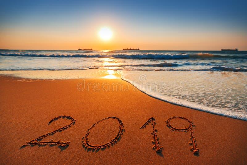 Conceito 2019 do ano novo feliz, rotulando na praia Nascer do sol do mar fotografia de stock royalty free