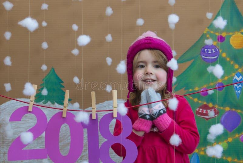 Conceito 2018 do ano novo Menina pequena bonita que decora o numeral do ano novo fundo de uma árvore de Natal pintada e imagem de stock