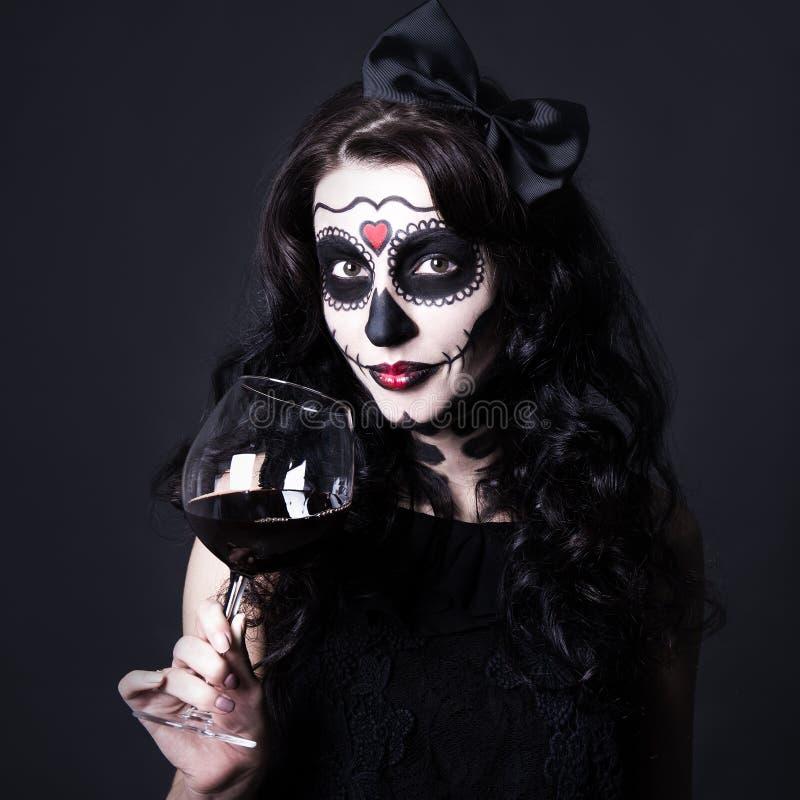 Conceito do apego de álcool - a mulher com crânio de Dia das Bruxas compõe h imagem de stock royalty free