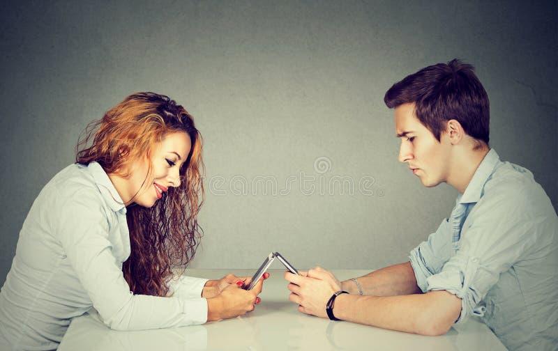 Conceito do apego de Smartphone Mulher e homem que sentam-se na tabela com o telefone esperto que ignora-se imagem de stock royalty free
