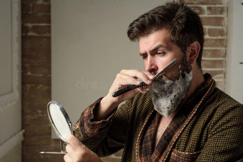 Conceito do barbeiro O cabeleireiro faz a penteado um homem com uma barba Barbearia de visita do cliente farpado Cuidado da barba fotos de stock royalty free