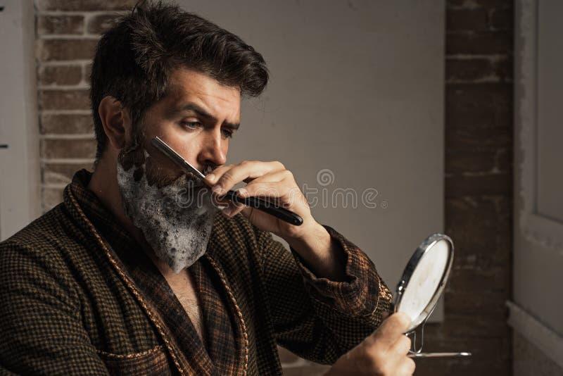 Conceito do barbeiro O cabeleireiro faz a penteado um homem com uma barba Barbearia de visita do cliente farpado Cuidado da barba fotografia de stock