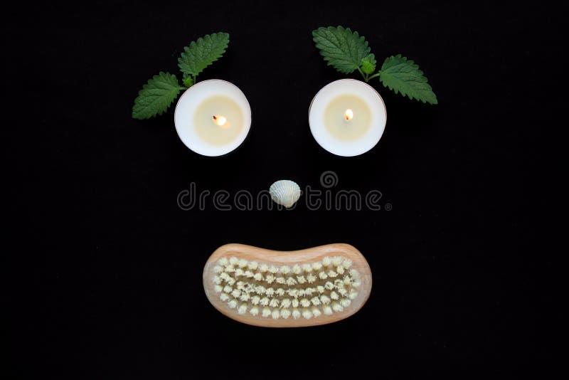 Conceito do bem-estar dos termas, cara com velas dos olhos, um nariz da concha do mar e uma boca de uma escova de madeira do corp imagens de stock