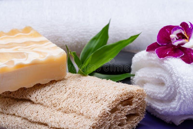 Conceito do bem-estar dos termas Esponja natural da bucha, sabão do leite da cabra da amêndoa, toalhas brancas, pedras do basalto fotos de stock