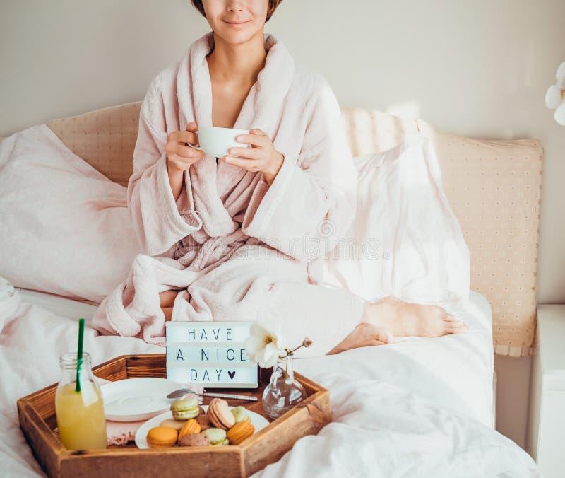 Conceito do bom dia A mulher de Croped no roupão que senta-se na cama, café bebendo e tem seu café da manhã na cama com tem um ag foto de stock royalty free