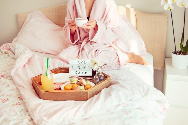 Conceito do bom dia O café da manhã na cama com tem um texto do dia agradável na caixa leve, no suco e nos bolinhos de amêndoa na fotografia de stock