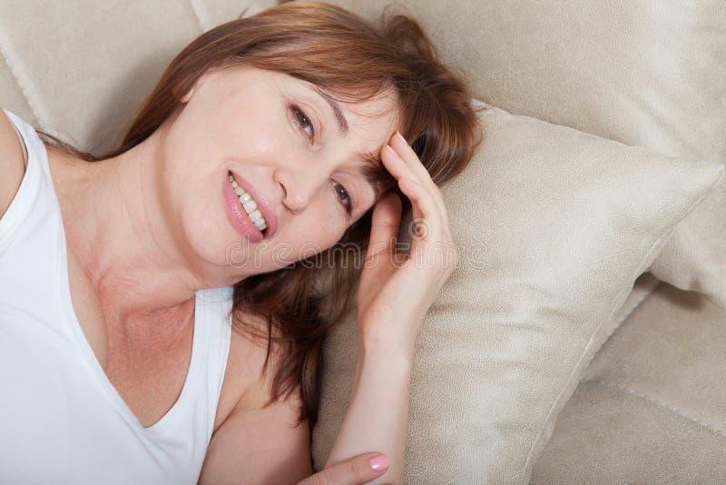 Conceito do bom dia Retrato da mulher da Idade Média que encontra-se no fundo da cama Vista superior e zombaria acima menopause imagem de stock