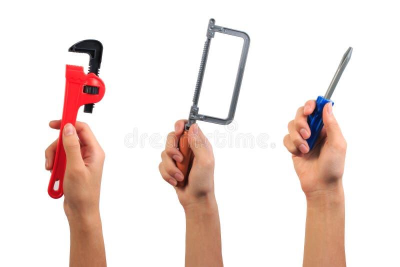 Conceito do brinquedo da ferramenta do coordenador A mão do menino que guardam a chave, a serra da fricção e a chave de fenda bri fotos de stock royalty free