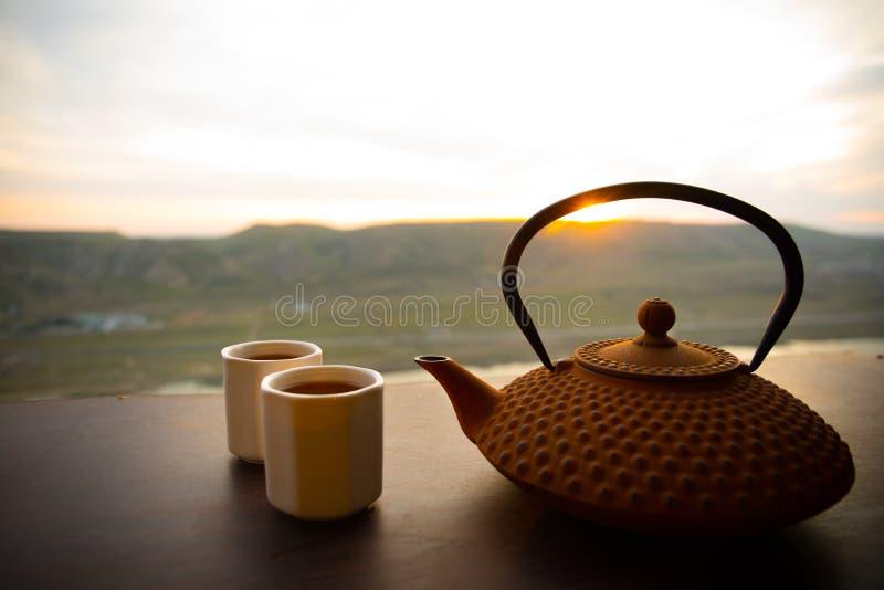 Conceito do ch? Bebida do leste da cultura japonesa da cerim?nia de ch? Bule e copos na tabela com as folhas de bambu no por do s fotos de stock royalty free