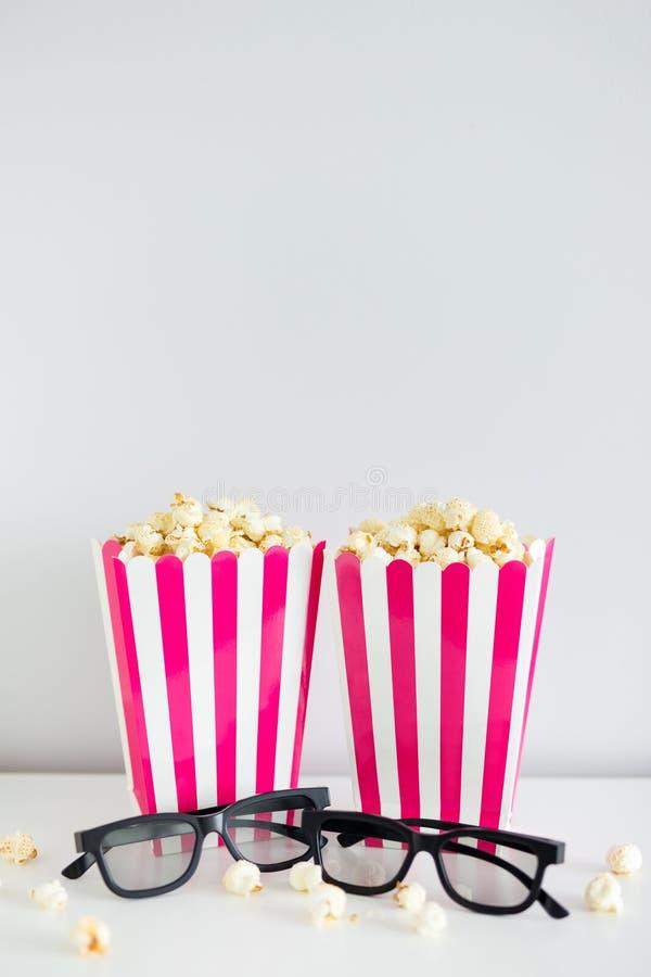 Conceito do cinema - duas caixas listradas vermelhas com pipoca e vidros 3d com espaço da cópia sobre a parede branca fotografia de stock